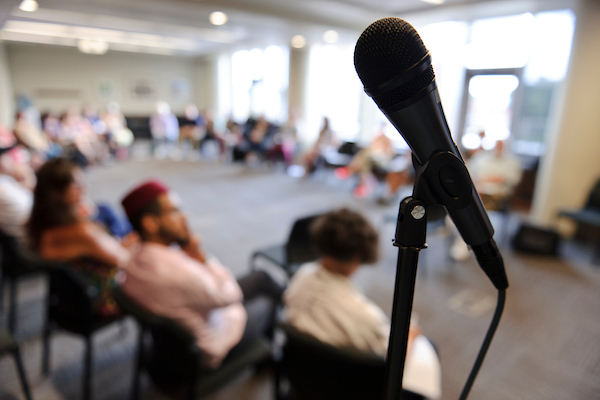 A microphone fills the foreground in front of a diverse group of more than 25 educators and community leaders.
