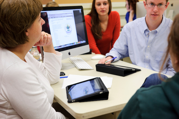 Katy Culver, left, a faculty associate in journalism and mass communication, facilitates an editorial-planning discussion with journalism students in a magazine-production class in Vilas Communication Hall.