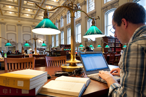 A graduate student studies using his laptop computer in Wisconsin Historical Society library reading room.