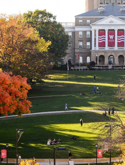 Tree foliage begins to take on a golden hue on Bascom Hill at the University of Wisconsin-Madison during autumn on Oct. 18, 2016. At top, red and white banners featuring an iconic W and the phrase