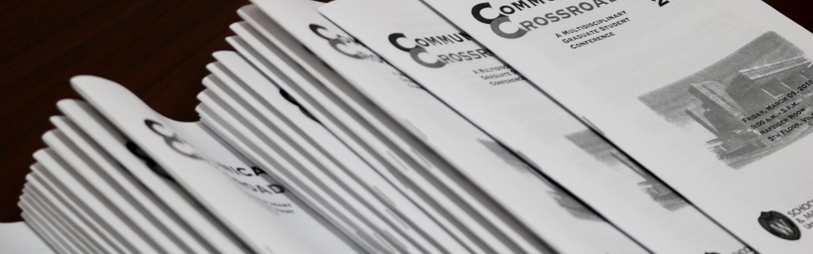A stack of programs from the Communications Crossroads conference 2018.