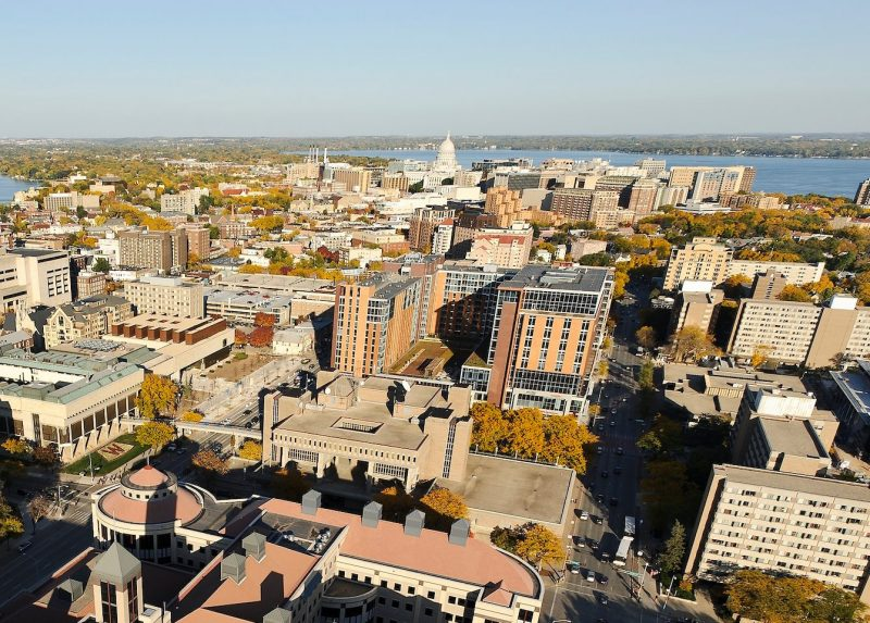 Grainger Hall is pictured in the foreground of an aerial view of the University of Wisconsin-Madison campus looking east toward the downtown Madison skyline during an autumn sunset on Oct. 5, 2011. Major campus facilities clockwise from left include Barnard Hall, Chadbourne Hall, Mosse Humanities Building, Chazen Museum of Art, Vilas Communications Hall, University Square, 333 East Campus Mall and Sellery Hall. On the horizon, left to right, are Lake Mendota, the Wisconsin State Capitol, and Lake Monona. The photograph was made from a helicopter. (Photo by Jeff Miller/UW-Madison)