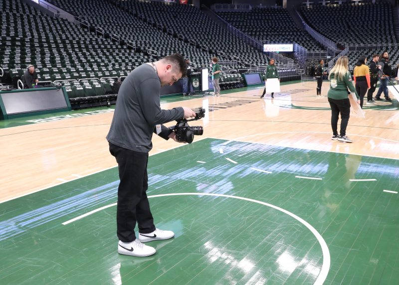 Rob Heimbruch on the Milwaukee Bucks' basketball court recording a video