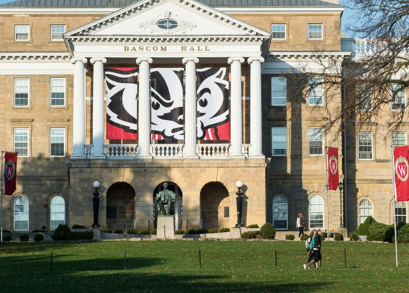 A newly designed banner with a graphic of mascot Bucky Badger's face hangs between the columns of Bascom Hall at the University of Wisconsin-Madison.