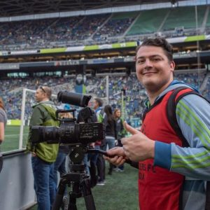 Rob Heimbruch poses on a soccer field behind his video equipment