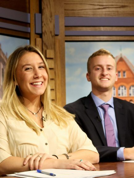 The Badger Report news desk with two anchors posing