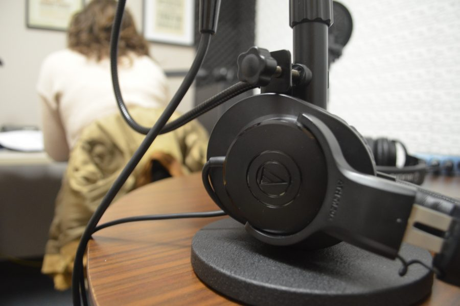 A pair of headphones in the foreground, with a person working at a computer in the background.