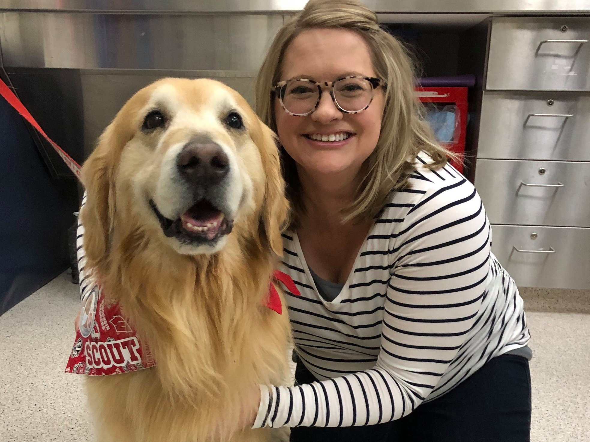 Photo of SJMC alum Ashley Voss posing with a golden retriever named Scout.