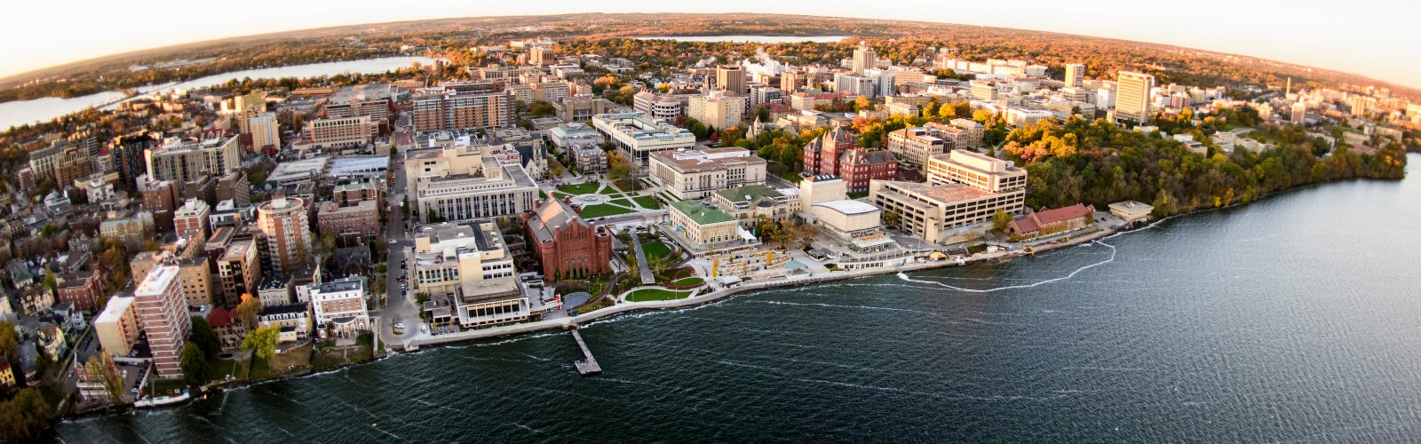 Lake Mendota and the University of Wisconsin-Madison campus, including the Memorial Union Terrace, are pictured in an early morning aerial taken from a helicopter on Oct. 23, 2018. This photograph was captured with a fisheye lens. (Photo by Bryce Richter /UW-Madison)
