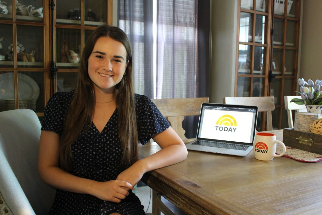 SJMC student Gracie Lund seated next to a laptop and coffee mug, both displaying the TODAY Show logo.