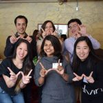 Six SJMC graduate students stand in two rows holding their index fingers and thumbs up in the shape of the Wisconsin W.