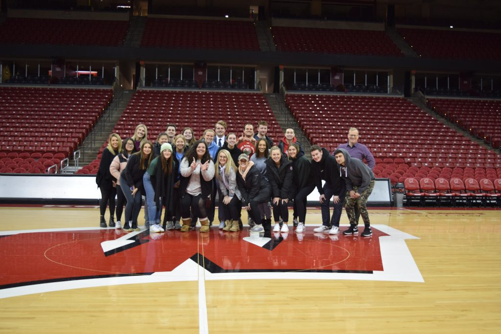 A group of students stands on the center of the basketball court at the Kohl Center on a large motion W logo.