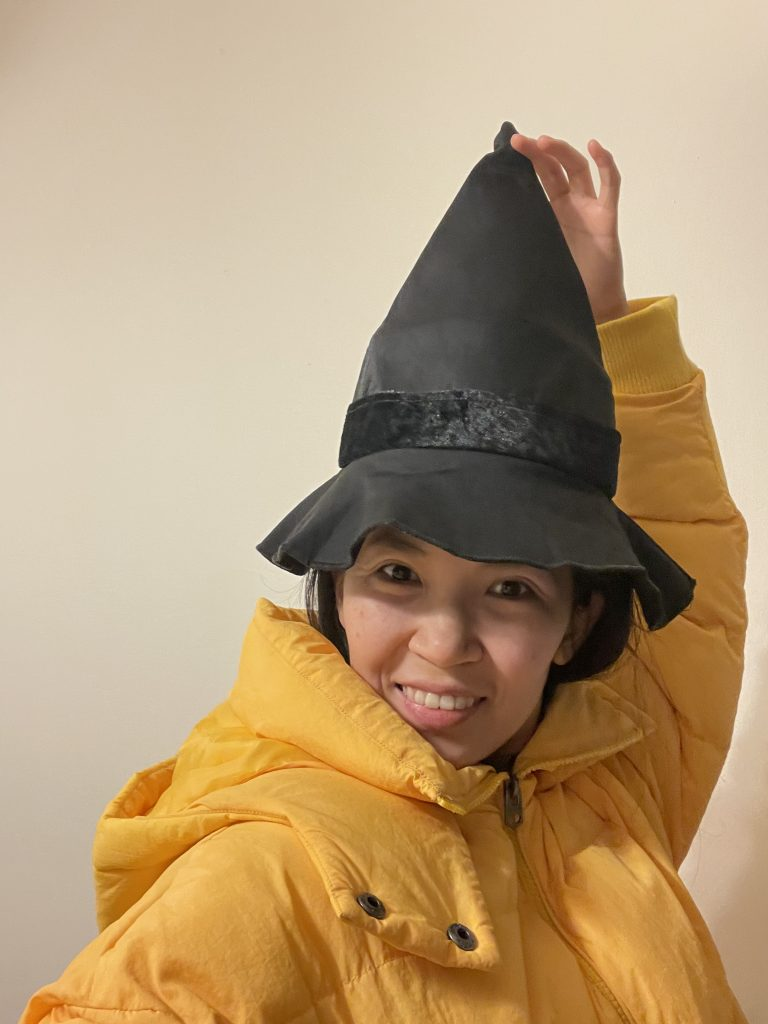 A woman in a yellow coat wearing a witch's hat, holding up the point of the hat over her head.