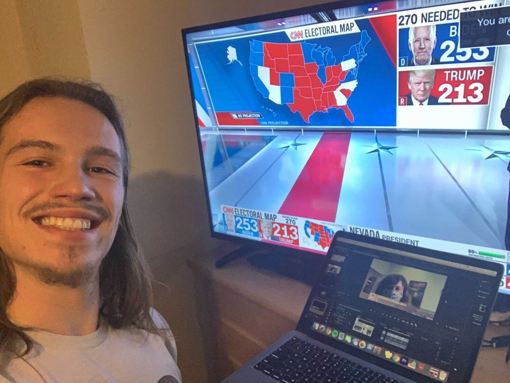 A man facing the camera next to a television screen displaying election results.
