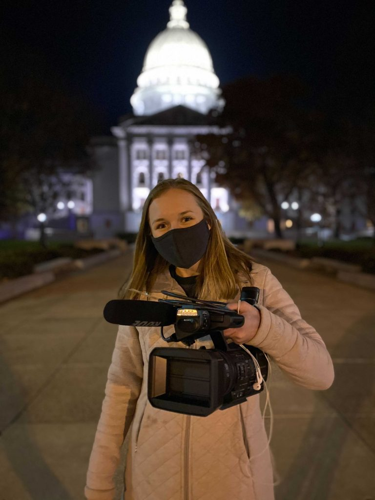 A woman in a face mask holding a video camera stands in front of the Wisconsin Capitol Building lit up at night.