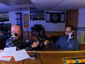 Two men toast with beer bottles sitting behind microphones in a rec room.