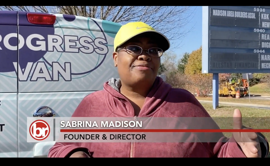 A woman in a baseball cap stands in front of the Progress Van. The photo is captioned 'Sabrina Madison, Founder & Director'.