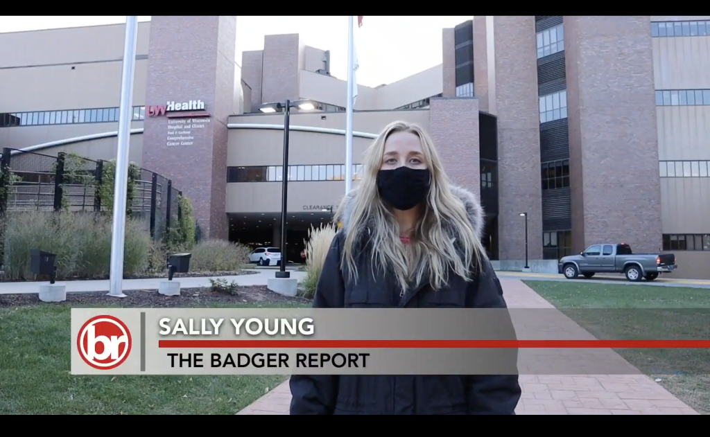 A woman in a face mask stands in front of the UW Carbone Cancer Center