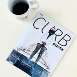 A print copy of Curb magazine laying on a white surface next to a cup of coffee.