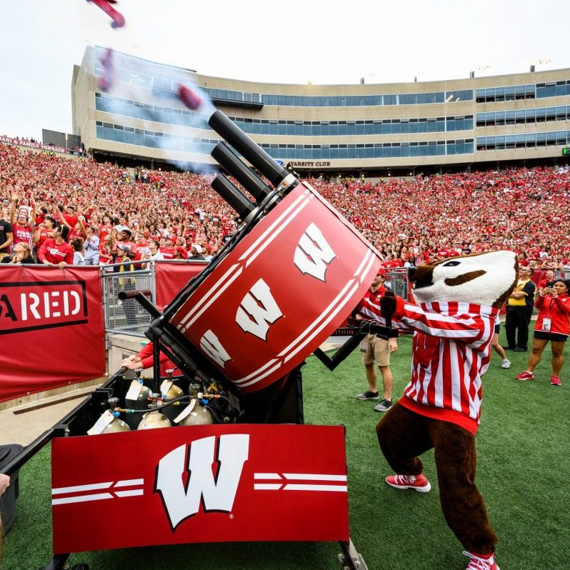 Bucky Badger fires a T Shirt cannon into the crowd at Camp Randall Stadium
