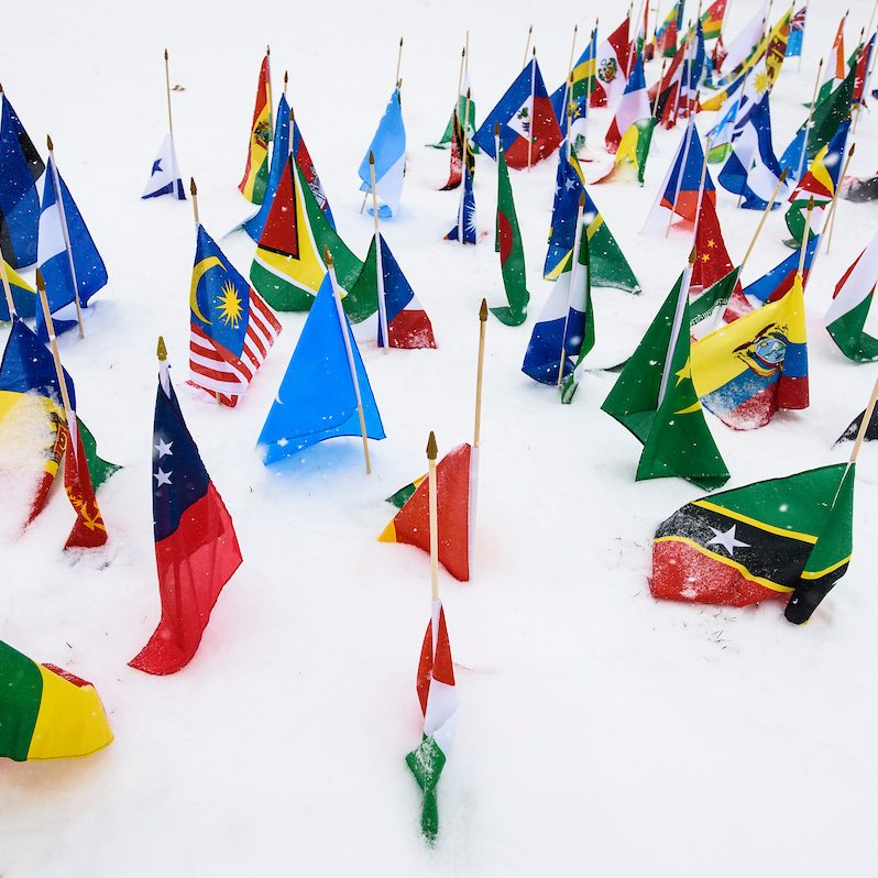 Flags from various countries stuck in the snow on Bascom Hill.