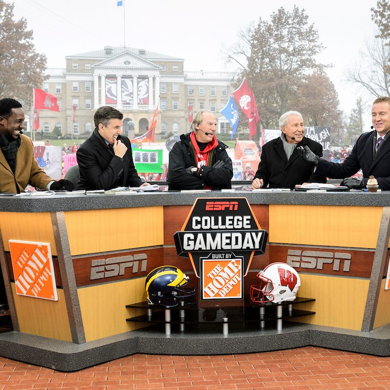 The anchors of ESPN College Game Day sit behind a desk with Bascom Hall in the background.