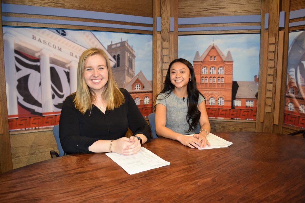 Two students sitting behind a news desk in the Wisconsin Public Television studios.