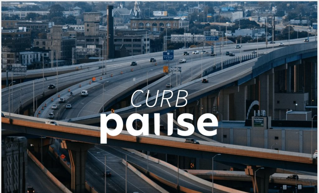An aerial photograph of a highway interchange with the Curb Pause logo superimposed on it