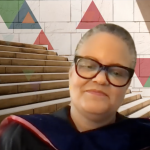 Lauren Tucker dressed in PhD regalia speaking to graduates via Zoom
