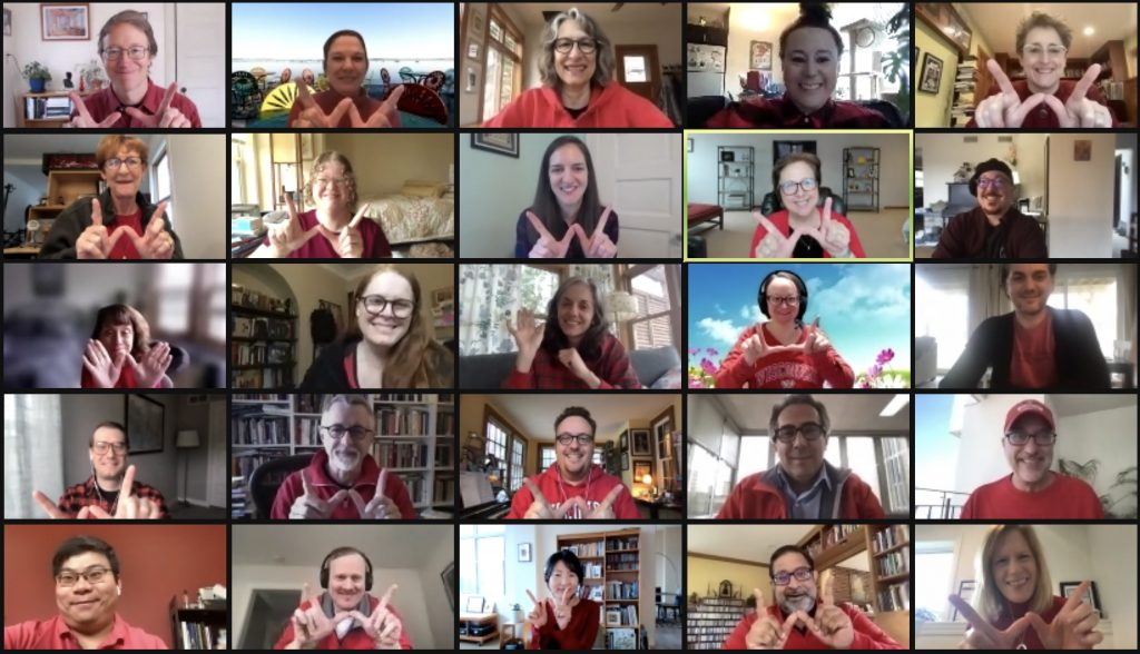A screenshot of a Zoom meeting featuring the faculty and staff of the SJMC wearing red and holding their hands up in the shape of a 'W'.