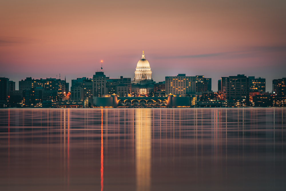 A panoramic shot of the Madison skyline from Lake Monona at dusk, featuring the Monona Terrace and Capitol building