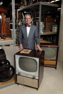 James Baughman, professor and department chair of Journalism & Mass Communication, poses with a 1953 Sylvania, foreground, and 1958 RCA television sets in the Wisconsin Historical Society's warehouse, March 26, 2007 at the University of Wisconsin-Madison. Baughman, an expert in Journalism history in 20th century and the beginnings of TV in America, recently published Same Time, Same Station: Creating American Televison, 1948-61. ©UW-Madison University Communications 608/262-0067 Photo by: Aaron Mayes Date:  03/07    File#:   D200 digital camera frame 9133